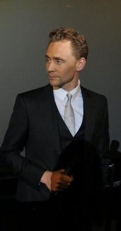 Tom Hiddleston wearing a three piece suit and getting distracted by someone or something.