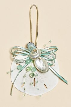 White sand dollar ornaments decorated with aqua ribbon and beads with pearlized shells for your coastal holiday tree!