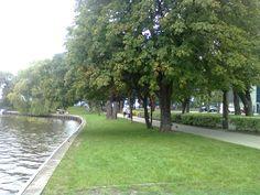 Pasaż w Ełku przy jeziorze. Dalej most i amfiteatr. Przy deptaku po prawej drewniane rzeźby królów i książąt Polski.