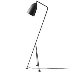 Gubi's iconic Gräshoppa lamp, designed by Greta Magnusson, was first introduced in 1947 and reissued in 2011. The signature form features a simple bell-like shade and a tilted tripod base with three legs.