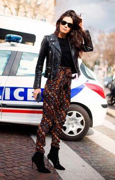 Street style look com blusa preta e calça estampada.