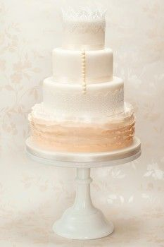 Isabelle is a four tier ombre cream ruffle wedding cake. A delicate representation of the bridal gown starting with the ruffles of the skirt, through to the lace and buttons on the bodice, and finished with a lace crown.