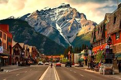 A view looking down the main shopping street in Banff, Alberta, Canada. This is a 'Must Visit Location'. Banff National Park is located just 90 km west of Calgary, Alberta, Canada making easy access to our international guests. Places Around The World, Oh The Places You'll Go, Places To Travel, Places To Visit, Banff Alberta, Alberta Canada, Jasper Alberta, Rocky Mountains, Parc National De Banff