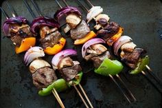 Marinade Ingredients: 1/3 cup olive oil 1/3 cup soy sauce 3 Tbsp red wine vinegar 1/4 cup honey 2 cloves garlic, minced 1 Tbsp minced fresh ginger Freshly ground black pepper to taste Kebab Ingredients: 1 1/2 lbs top sirloin steak, cut into 1 1/2-inch cubes 1 large bell pepper 1-2 medium red onions 1/2 to a pound button mushrooms About 20 bamboo or wooden skewers METHOD 1 Mix the marinade ingredients together in a bowl and add the meat.