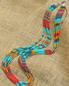 Bright seed bead multi strand patterned statement necklace. Blue, teal, red, orange seed beads.