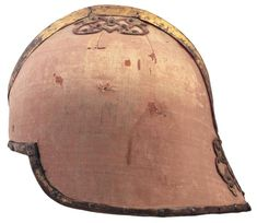 A ceremonial sallet, celata da pompa alla veneziana, Venice, second half of the 17th century-first half of the 18th century. With copper skull apparently made in one piece and with a low medial ridge, covered with red silk velvet and fitted with gilt-copper bands around the edges and over the medial ridge, with further gilt plaques pierced with arabesques and riveted onto the upper and the rear parts of the skull