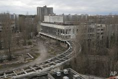 This photo taken Wednesday, March 23, 2016 shows abandoned apartment buildings in the town of Pripyat near Chernobyl, Ukraine, with a chimney, left, at the destroyed reactor and a gigantic  arch-shape confinement to cover the remnants of the exploded reactor, in the back, at the Chernobyl nuclear power plant. Thirty years after the world's worst nuclear accident, the Chernobyl nuclear power plant is surrounded by both a hushed desolation and clangorous activity, the sense of a ruined past…