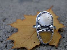 A perfect triangle of rare yellow sea glass is set in a fine silver serrated bezel. This gem is paired with a beach stone, which is set in a