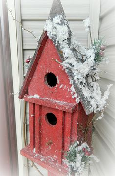 red birdhouse with faux snow and greenery