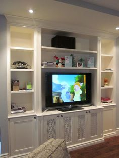 Decor that doesn't distract around the television. // I'd really like a big shelving unit-esque thing like this--looks clean and sleek and hides so much stuff! Also integrates the tv without having to hang it on the wall or put it on the fireplace (a cardinal sin of decorating in my book)
