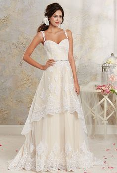 Modern Vintage by Alfred Angelo. Romantic tiered gown in soft satin, tulle and re-embroidered lace appliqu�. Sweetheart bodice accented with matching lace straps. Retro-inspired moonstone style beading at the natural waist. A-line skirt features a tiered high-low hemline. Detachable full length skirt and small sweep train.