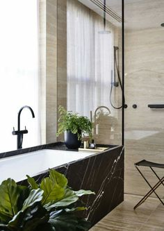 This striking bathroom by Agushi Constuctions combines luscious timber paneling and opulent stone surfaces to create a warm and masculine space, featuring Sussex Taps #Scala collection in Matte Black. #SussexTaps #CraftedInMelbourne #Scala