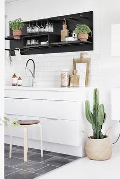 Une cuisine blanche avec des carreaux type métro en crédence , du carrelage gris au sol et des plantes vertes dont dont un cactus avec un panier en osier comme cache pot