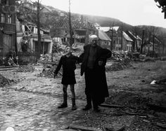 An old man leads an injured boy to a U.S. aid station after the German boy picked up a pair of rigged shoes. Altenbunden, Germany.