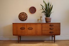 Mid-Century Danish Modern teak credenza. Made in the UK by Beautility. Unique afrormosia handles. Curve on the face of credenza. Left door opens out and the center cabinet is drop down; both co...