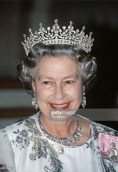 The Queen Smiling During A Royal Tour. She Is Wearing A White Crepe Evening Dress Embroidered With Silver By Designer Ian Thomas. The Queen Is Wearing A Tiara With A Ruby And Diamond Flower Motif Known As Queen Mary's Girls Of Great Britain And Ireland Tiara. Her Diamond Necklace Is The King Faisal Of Saudi Arabia Necklace.