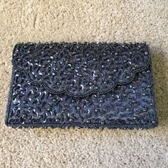 Silver/ Gray Beaded & Sequenced Clutch NWOT silver/ gray clutch with a beautiful sequence and beaded design. It closes with a magnetic button and has a beaded strap to wear as a purse. It's silk material. Bought this, but never wore it it's really beautiful. Bags Clutches & Wristlets