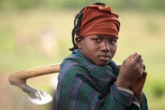 An adolescent girl carriers a hoe over her shoulder as she heads to work in a vegetable garden, in the village of Noussou, Nord Region of Burkina Faso.  The garden is run by a collective of 54 women who each manage one hectare of land vegetables year-round despite seasonal interruptions. The region is participating in the UNICEF/European Union-supported nutrition security programme.  © UNICEF/Olivier Asselin  http://www.unicef.org