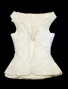 1700-20 Waistcoat - Fine linen top and coarse linen underneath, quilted all over with cream 20 ply silk in back stitch. Design of small feathers and 'rose window' marguerites threaded with twisted sheeps wool. Ground of small lozenges. Fronts curve away - slashed at sides and centre back. Sleeveless. 9 eyelets oversewn for front lacings. (female)
