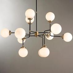 "Mid-Century Parlor Chandelier This chandelier is incredibly stylish and architecturally inspired. Its airy frame maintains a refined look while the 12 globe-style lights provide ample lighting. Choose from Antique Brass with White glass or Polished Nickel with Clear glass. 12x40 watt candle base lamps max. (29""Hx47""W)"