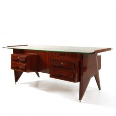 Desk, Dassi Mobili Moderni, Lissone  Italy, 1950s. Rosewood construction with glass top, four locking drawers; brass fittings and feet.