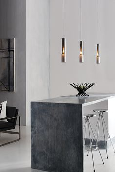 The Matan LED pendant light from Tech Lighting features a slim artisan molded glass shade treated with a special mirror like coating. When not illuminated, the shade's subtle opacity disappears as its outer surface resembles chrome-plated metal. The lower section of each shade includes a series of organically flowing rings created by a delicate etching process, adding dimension. Ideal for kitchen island or dining room lighting.