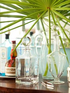 Tabletop Collection  Even in the smallest details, tropical blues and greens are played up throughout the home. Here, a collection of glass bottles creates an elegant assembly on a vintage wooden table. A mirror hung behind the display reflects light and multiplies the bottles' sparkle.