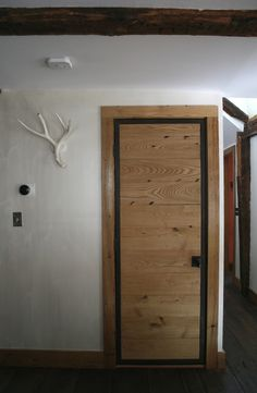 Door made with an acid washed steel frame with a reclaimed chestnut face. Door and trim by Erik Block Design Build.