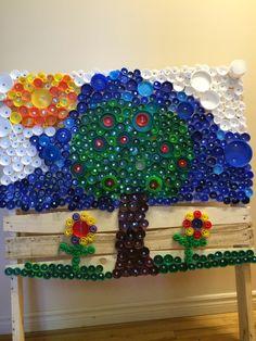 Projet d'art: bouchons de plastique récupérés et vissés sur une palette de bois recyclé. Classe de maternelle 5ans.