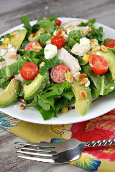 Recipe for Spinach Salad with roasted chicken, avocado, goat cheese, tomato, corn and toasted pine nuts- tossed in a tangy Dijon vinaigrette. Photo included.