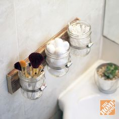 Hose clamps, mason jars and a nice wooden board make for an attractive, affordable bathroom storage solution.