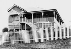 Lorenz family home on an elevated block at Armitage Street in Lota, Brisbane, ca.1910 Highset wooden home in Lota with a bungalow-roof and verandah on two sides. French doors at the front of the house open onto the verandah. The house was situated at 37 Armitage Street, on the corner of Ernest Street. A man and woman stand at the top of the front steps, probably Mr and Mrs Lorenz
