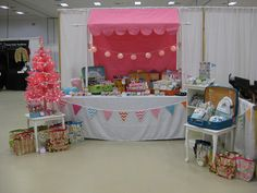 Pretty craft booth.  Love the pink Christmas tree! Suitcases - easy to pack away the goods afterwards.