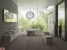 """The epitome of Los Angeles living is bringing the feeling of the outdoors inside a house. The floor to ceiling glass wall in this bathroom exposing the greenery creates an organic atmosphere of nature and light. The clean lines of rustic stone and wood finishes are warm and inviting. """"Warm contemporary"""" is a commonly used  label for this type of interior design."""