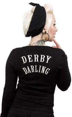 """SOURPUSS DERBY DARLIN CARDIGAN  Keep cozy warm when your not in the rink with the Derby Darlin' cardigan! This black cardigan features embroidered derby gal legs on the chest, red buttons & """"Derby Darling"""" embroidery on back.  $50.00"""
