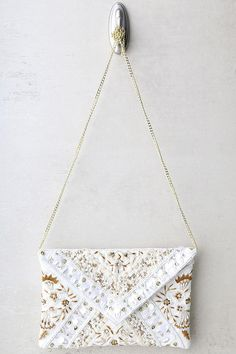 "The Hallelujah Cream Beaded Clutch will have you thanking the heavens you found it! Dazzling gold, cream, and ivory beaded patterns decorate this classic envelope clutch. Lift the top flap from the magnetic closure to utilize the interior wall compartment. Attached shiny gold chain strap measures 40"" long."