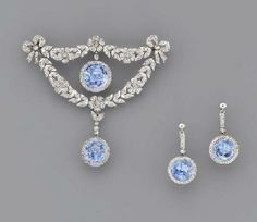 A BELLE EPOQUE SAPPHIRE AND DIAMOND BROOCH AND A PAIR OF EAR PENDANTS   The central circular-cut sapphire and diamond cluster drop within the rose-cut diamond floral wreath with diamond bow terminals, suspending a sapphire and diamond drop, earrings en suite, adapted, mounted in platinum, circa 1905,