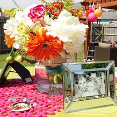 Personalized Celebration for the High School Graduate: using floral arrangements and framed photos as centerpieces
