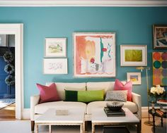 funky fun living room with blue wall, white couch, colored pictures and gallery wall. Good stuff :)