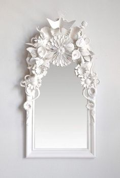 Random items glued to a mirror frame and spray painted...I've done this with silk dollar store flowers and a second hand chandelier!