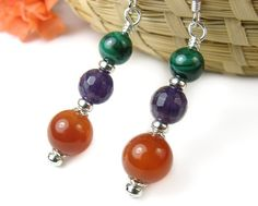 These gemstone earrings bring together carnelian, amethyst, and malachite beads in an earthy stack-designed pair of handmade dangles. All the metal
