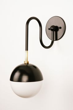L 11in (28cm) x W 6in (15cm) x H 16in (41cm) Canopy: Dia 5in (13cm) Playful and graphic the Balise collection is inspired by the 1960s and the irreverence of Jean Royère. The sconce is fabricated from either brass or black powder-coated steel with pure brass details and a 6in (15cm) opal glass globe