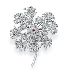 A DIAMOND AND RUBY FLOWER BROOCH, BY RENE BOIVIN A DIAMOND AND RUBY FLOWER BROOCH, BY RENE BOIVIN Mounted en tremblant, designed as an circular-cut diamond Queen Anne's Lace flower blossom, set with a circular-cut ruby pistil, with circular-cut emerald and sculpted gold leaves and a baguette-cut diamond stem, mounted in platinum and 18k gold, 1938, with French assay marks Signed René Boivin, G & Co. for Gattle & Co. Photo courtesy of Christie's