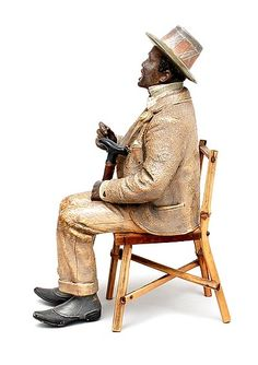 Polychrome painted terracotta seated figure with monocle and cane on bamboo wooden chair execution attributed to Friedrich Goldscheider Vienna / Austria ca.1895
