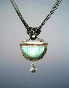 Asian Bowl Pendant This unusual pendant is made with a bright greenish blue Spectrolite cab from Finland. When the light reflects from inside the stone, a brilliant flash of green/blue is seen. The bezel is made with Art Clay Silver and is formed, fired and finished by hand. I am working on bezel setting, practicing over and over and over again so that I can actually produce something worth looking at. These Spectrolite stones are tricky because you have to orient them so the light hits them…
