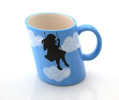 Whimsical tilted mug featuring a girl on a swing  Limited edition only.    This handmade mug features a beautiful blue sky with soft white puffy clouds,