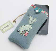 Handmade Phone cover from a beautiful quality wool fabric this can be used as a phone or i-pod cover. Available in a beautiful blue or green wool, but can be made in alternate colours on request.Decorated with a beautiful rabbit in a co-ordinating cotton fabric this comes fully lined in the same gorgeous cotton, and finished with ribbon and a popper stud to secure. Would make a fabulous gift or even better, a treat for yourself! Due to the handmade nature of this product slight variations…