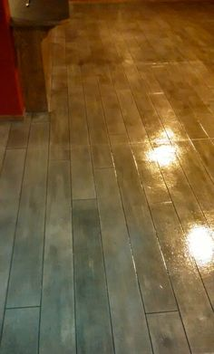 Basement floor restoration using a concrete overlay to replicate grayed barn wood in an Omaha, NE home.