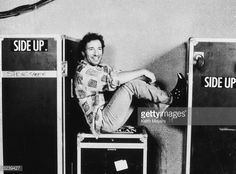 American musician Bruce Springsteen sits on a trunk with his feet up backstage at the Brendan Byrne Arena in the Meadowlands sports complex East...