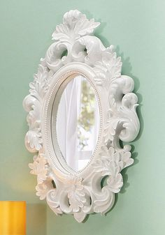 Mit aufwendig gearbeitetem Rahmen aus Polyresin. In zwei Farben: Hochglanz weiß oder schwarz lackiert. Mit ovaler Spiegelfläche: ca. 24/37 cm.  Gesamtmaße (B/T/H): 52/7/80 cm....